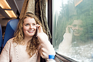 Smiling teenage girl in train car on cell phone - HAPF000229