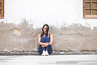 Young woman sitting outdoors at a wall - SIPF000173