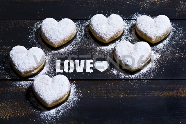 The word 'Love' stenciled with icing sugar and six heart-shaped crullers on dark wood - MAEF011281 - Roman Märzinger/Westend61