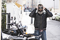 Spain, Jaen, biker putting on his motorcycle goggles - JASF000392