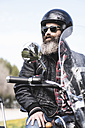 Portrait of bearded biker wearing helmet and sunglasses sitting on his motorcycle - JASF000398