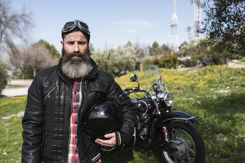 Portrait of biker standing on a meadow in front of his motorcycle - JASF000401