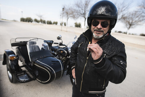 Portrait of cool biker wearing helmet and sunglasses standing on a road in front of his sidecar motorcycle - JASF000404