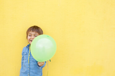 Smiling little boy with green balloon and streamer standing in front of yellow wall - VABF000144