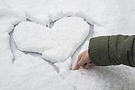 Finger of little boy carving a heart in snow on a car - DEGF000611