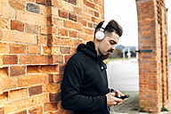 Portrait of young man listening music with headphones - MGOF001429