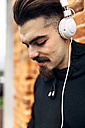 Portrait of young man listening music with headphones - MGOF001432