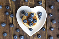 Blueberries and stack of mini pancakes on a heart-shaped plate - SARF002551