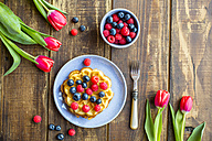 Waffle with blueberries and raspberries on plate, tulips on wood - SARF002558