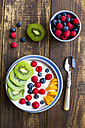 Bowl with yogurt and blueberries, kiwi, mango and raspberries, spoon on wood - SARF002561