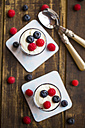 Yogurt with red fruit jelly, blueberries and raspberries in glasses on wood - SARF002564