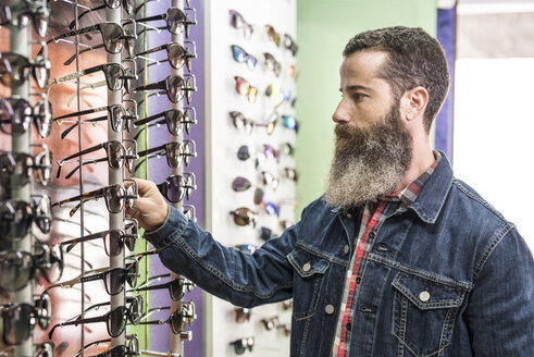 Bearded man in optical store chosing glasses - JASF000411