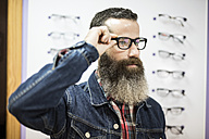 Bearded man in optical store trying on glasses - JASF000417