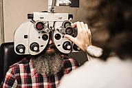 Bearded man at the optometrist making an eye test - JASF000420