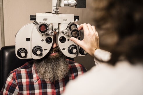 Bearded man at the optometrist making an eye test - JASF000420