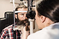 Optometrist examining eyes of a bearded man - JASF000423
