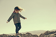 Spain, Consuegra, little girl walking on rocks in the mountains - ERLF000136