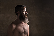Portrait of bare-chested man with long beard in front of brown background - JASF000426