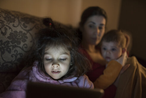 Portrait of little girl using digital tablet at home while mother and little brother watching her - JASF000432