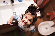Portrait of smiling little girl standing in the bathroom going to brush her teeth - JASF000435