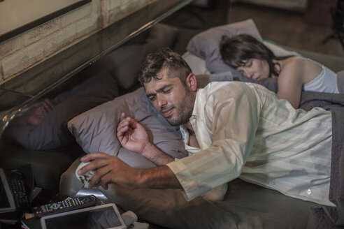Man sleepless in bed looking at alarm clock with wife lying beside him - ZEF008419