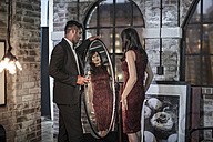 Well-dressed couple in an apartment with woman looking in mirror - ZEF008458