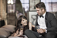 Smiling couple in elegant clothing drinking champagne in bed - ZEF008461