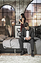Elegant man on bed getting dressed with wife in background - ZEF008464