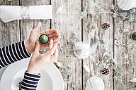 Girl's hands holding tea light in front of laid table at Christmas time - LVF004532