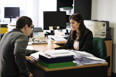 Man and woman in office sitting opposite looking at document - JASF000470