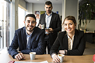 Portrait of smiling man and woman sitting at office desk with coffee - JASF000473