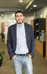 Portrait of smiling young man in office - JASF000476