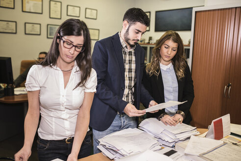 Three colleagues in office looking at documents - JASF000485