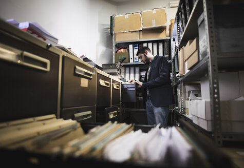 Man searching for files at basement - JASF000488