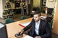 Man working at desk in office with Christmas tree in background - JASF000497