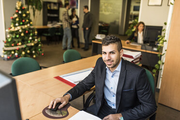 Portrait of smiling man working at desk in office with Christmas tree in background - JASF000500