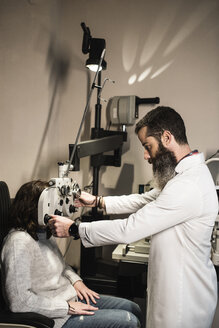 Optometrist examining woman with a phoropter - JASF000513