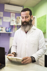 Bearded man in lab coat at store counter looking down - JASF000519