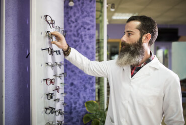 Bearded optometrist in his store looking at glasses - JASF000525