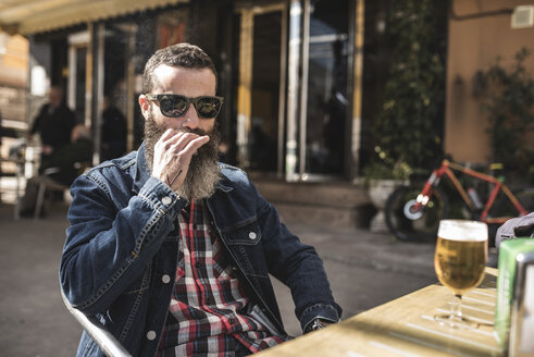 Portrait of bearded man wearing sunglasses smoking cigarette at outdoor gastronomy - JASF000528