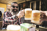 Portrait of bearded man wearing sunglasses toasting with mug of beer at outdoor gastronomy - JASF000531