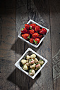Bowl of pineberries and bowl of strawberries on wood - CSF027094
