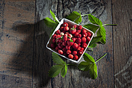 Bowl of wild strawberries and leaves on wood - CSF027142
