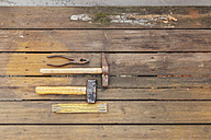 Row of four tools lying on rotten balcony floarboards - GWF004627