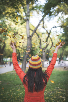 Back view of woman wearing woolly hat throwing autumn leaves in the air - DEGF000639