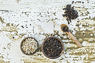 Two wooden bowls of black and white peppercorns - ASF005840