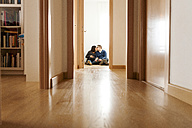 Expecting parents sitting on floor of flat, kissing - VABF000150