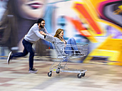 Young man pushing woman in shopping cart, laughing and running - LAF001607