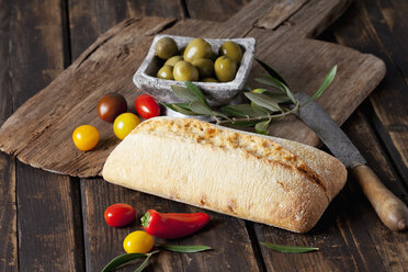 Ciabatta bread with green olives in bowl, tomatoes and mini capsicum on wood - CSF027163