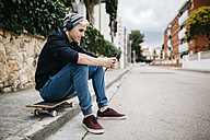 Spain, Torredembarra, smiling young man sitting on his skateboard at curb listening music with headphones - JRFF000443